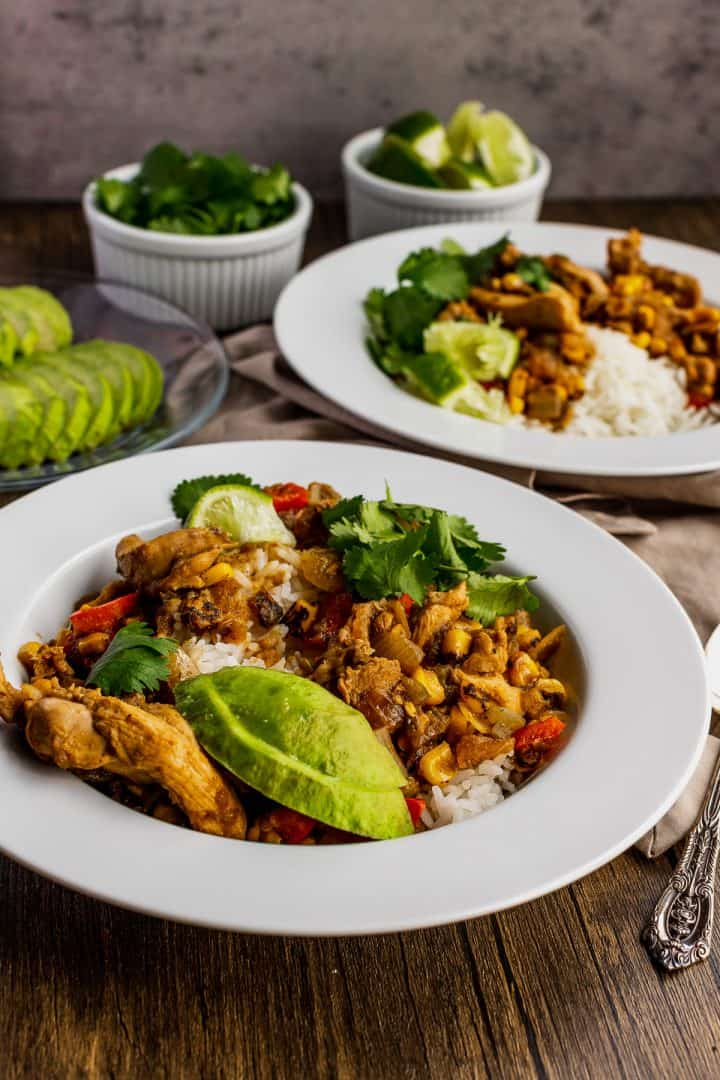 two bowls of salsa verde with chicken and a few bowls of good toppings such as avocado, lime wedges, and cilantro
