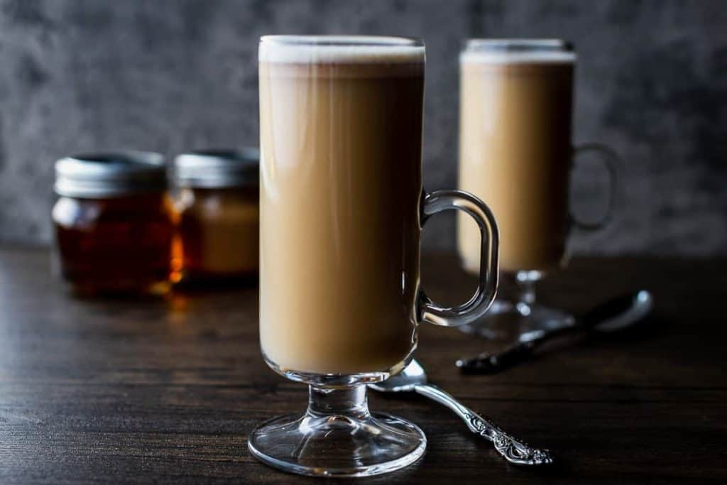 two hot buttered rums in tall glasses on a dark background