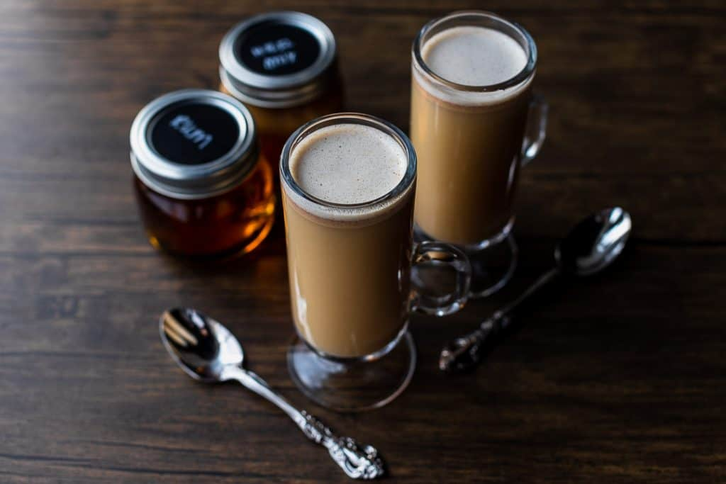 two hot buttered rums with jars of batter and rum