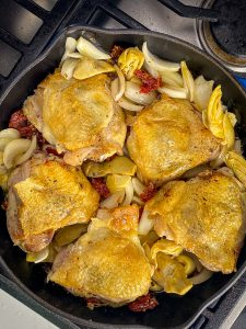 chicken nestled among sundried tomatoes, artichokes and onion