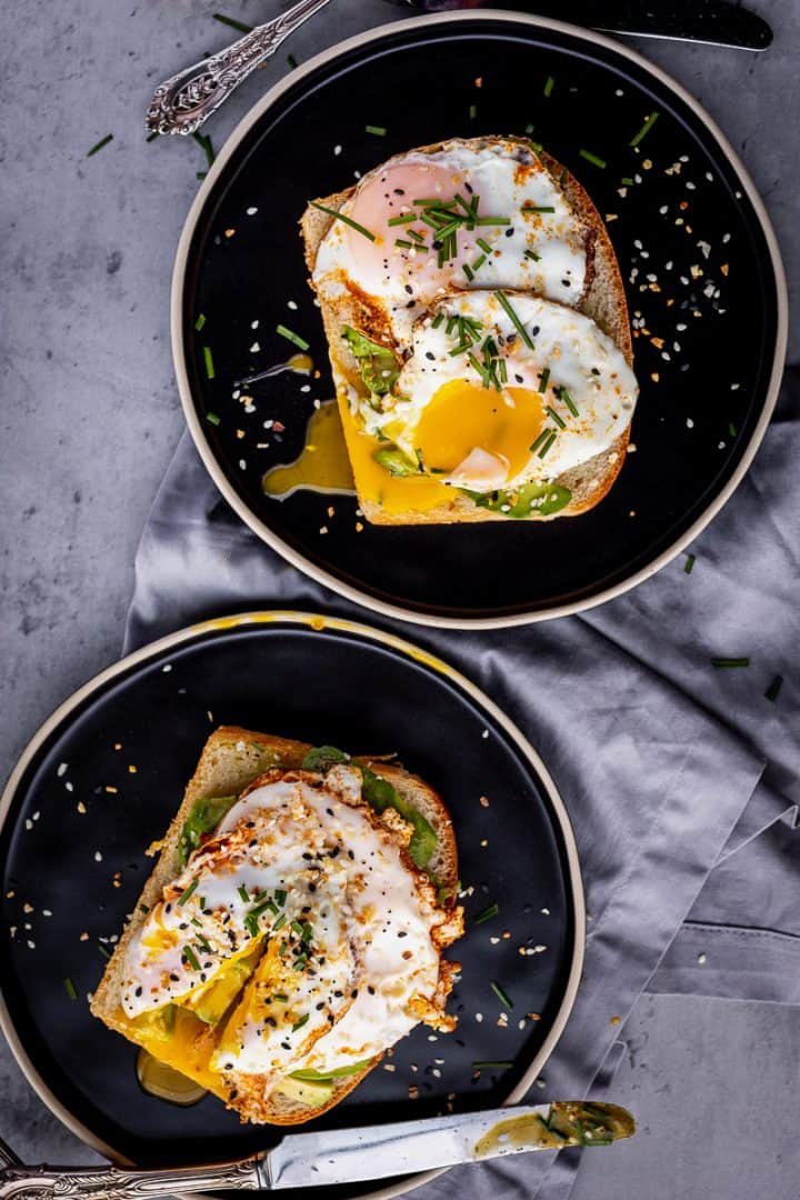 two pieces of avocado toast with two eggs on each toast, broken open to show yolks