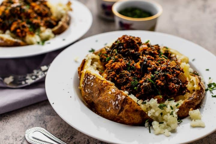 two plates of sloppy joes stuffed into potatoes with a side of chives