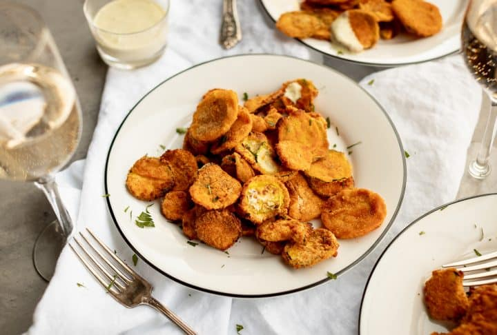 a table of plates with zucchini chips and ranch