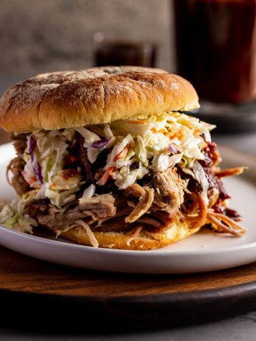 coleslaw piled on a pork sandwich with bbq sauce in the background